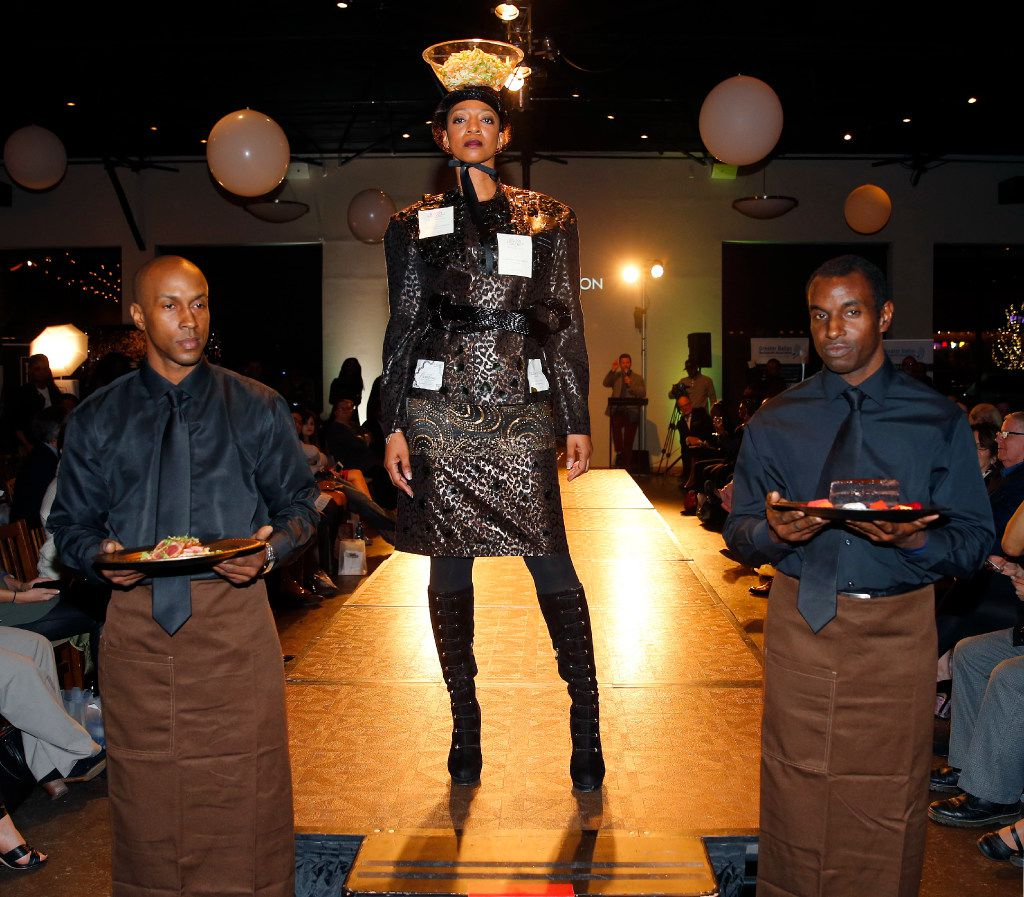 A model supports a bowl of salad on her head as she models a dress designed by Baqash Wilson under the label Konjo Collection during the Food in Fashion event at 3015 in the Trinity Groves.