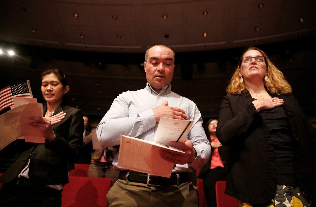New U.S. citizens (from left) Supinya Phapant of Thailand, Julio Martinez of El Salvador and Mary McCarthy of Canada recite the Pledge of Allegiance during a naturalization ceremony at the George W. Bush Presidential Center in Dallas on March 18, 2019.