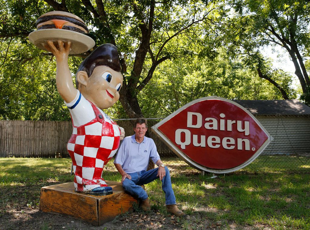 Gary Isett poses next to the Big Boy statue that's caused so much buzz about his lawn. Next to him is his 9-foot Dairy Queen sign, which he says is more unusual than McDonald's or Burger King signs.