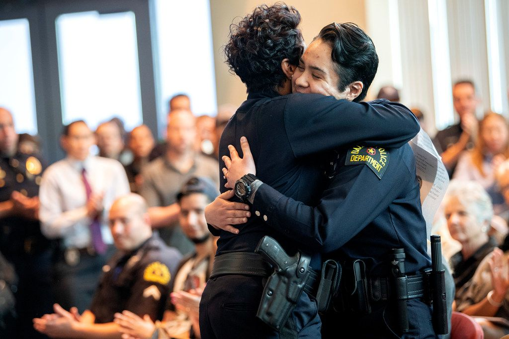 Dallas police officer Crystal Almeida, right, receives a hug from Chief U. Renee Hall.