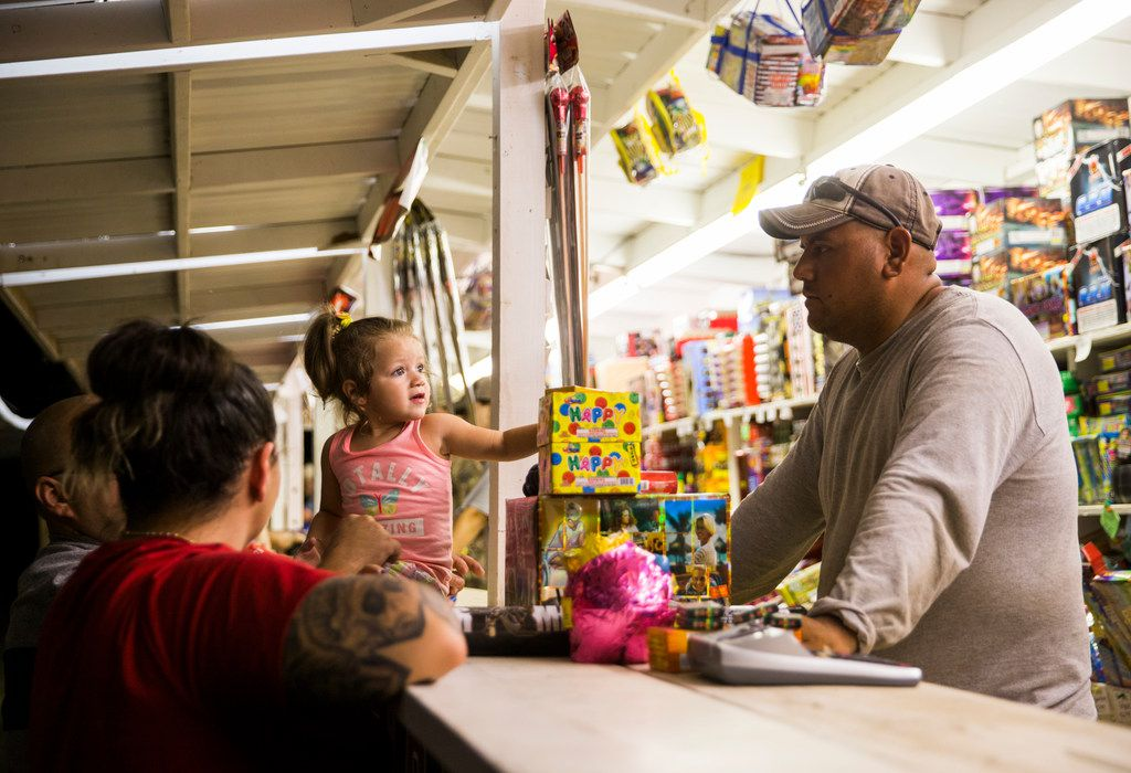 Lola Gomez looks at Chris Gomez as she adds to a pile of fireworks for Chris and Taren Gomez at Palmer Fireworks in Dallas.