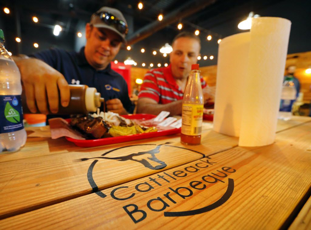 Mike Kelly of Melissa, Texas (left) and Shawn Moody of Allen, Texas, settle in with tray full of meats at the newly reopened CattleAck BBQ, Wednesday, July 7, 2016.  The restaurant doubled in size of their location at 13628 Gamma Rd. in North Dallas.