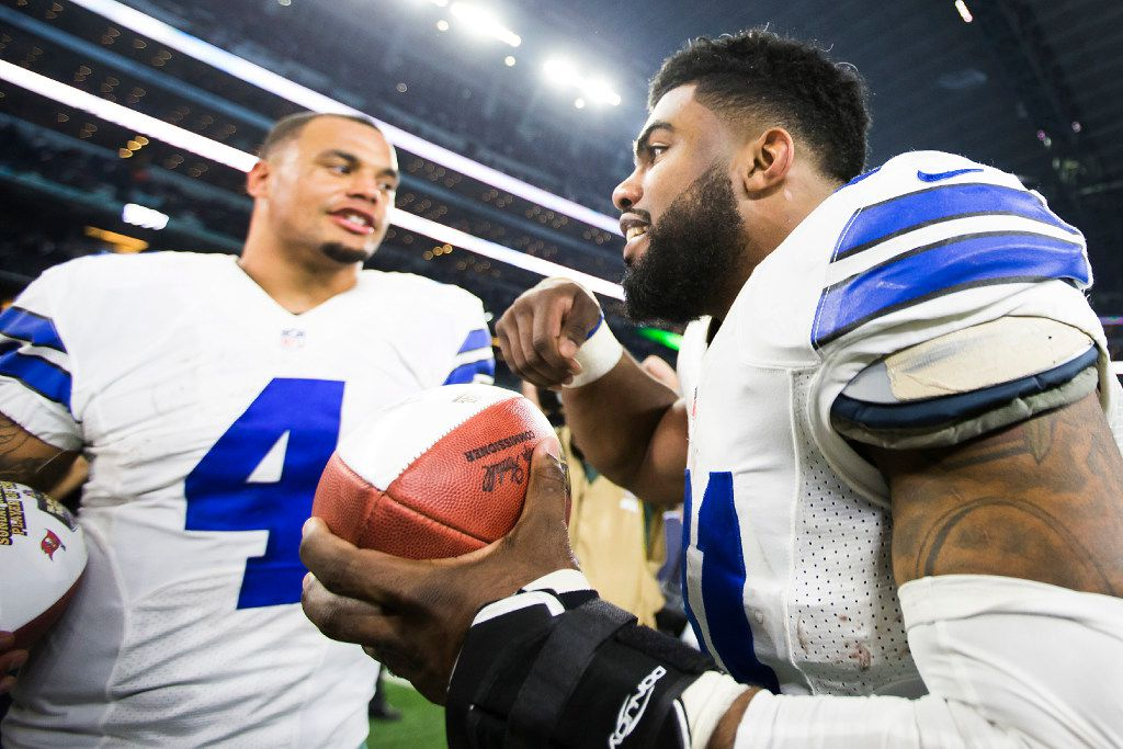 Dallas Cowboys quarterback Dak Prescott (4) celebrates with running back Ezekiel Elliott (21) after a win over the Tampa Bay Buccaneers in an NFL football game at AT&T Stadium on Sunday, Dec. 18, 2016, in Arlington. The Cowboys won the game 26-20. (Smiley N. Pool/The Dallas Morning News)