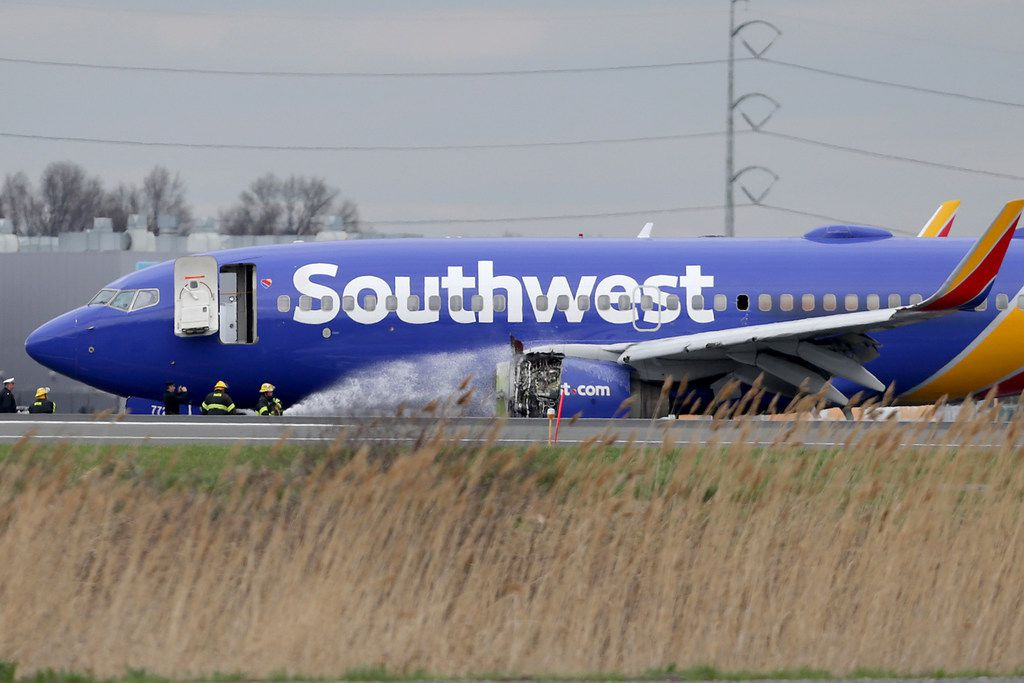 Firefighters spray a Southwest Airlines plane with a damaged engine at Philadelphia International Airport on April 17, 2018.
