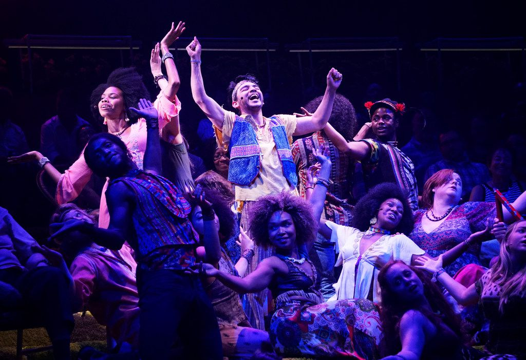 Tiana Kaye Johnson as Sheila and Christopher Llewyn Ramirez as Woof performing amid the cast of  Hair,  presented by DallasTheater Center at the Wyly Theatre.