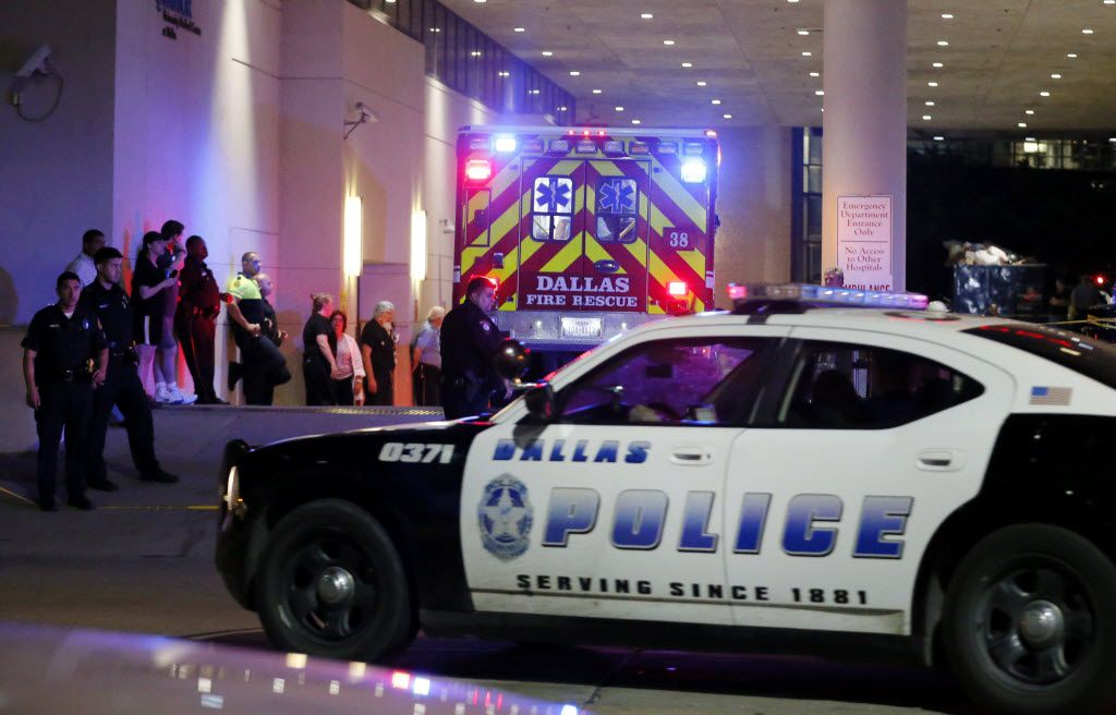 A Dallas police vehicle follows behind an ambulance carrying a patient to the emergency department at Baylor University Medical Center, as police and others stand near the emergency entrance early Friday, July 8, 2016, in Dallas. At least two snipers opened fire on police officers in Dallas on Thursday night during protests over two recent fatal police shootings of black men, police said. (AP Photo/Tony Gutierrez)