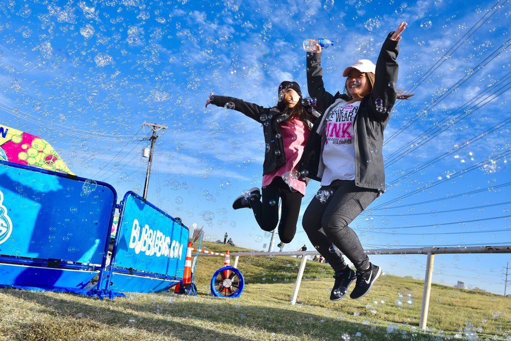 University of Arlington students Rachael Na, 23, left, and Cindy Nguyen, 24, get revved up for the Making Strides Against Breast Cancer 5K on Oct. 28, 2017 near the Margaret Hunt Hill Bridge in Dallas.