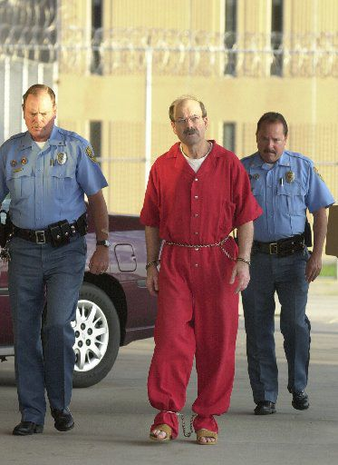 Convicted serial killer Dennis Rader, known as BTK, walks into the El Dorado Correctional facility with two Sedgwick County sheriff's officers Friday, Aug. 19, 2005, in El Dorado, Kan. Rader was convicted for killing 10 people in a 30-year span and sentenced to 10 consecutive life terms.
