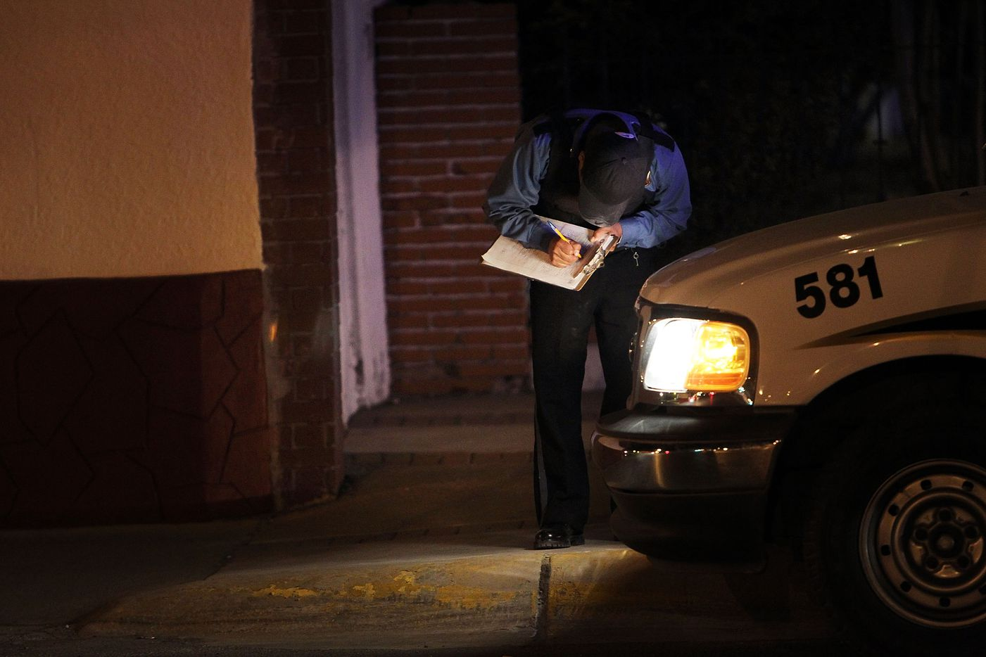 A police officer takes notes at an early morning murder on March 26, 2010 in Juarez, Mexico.