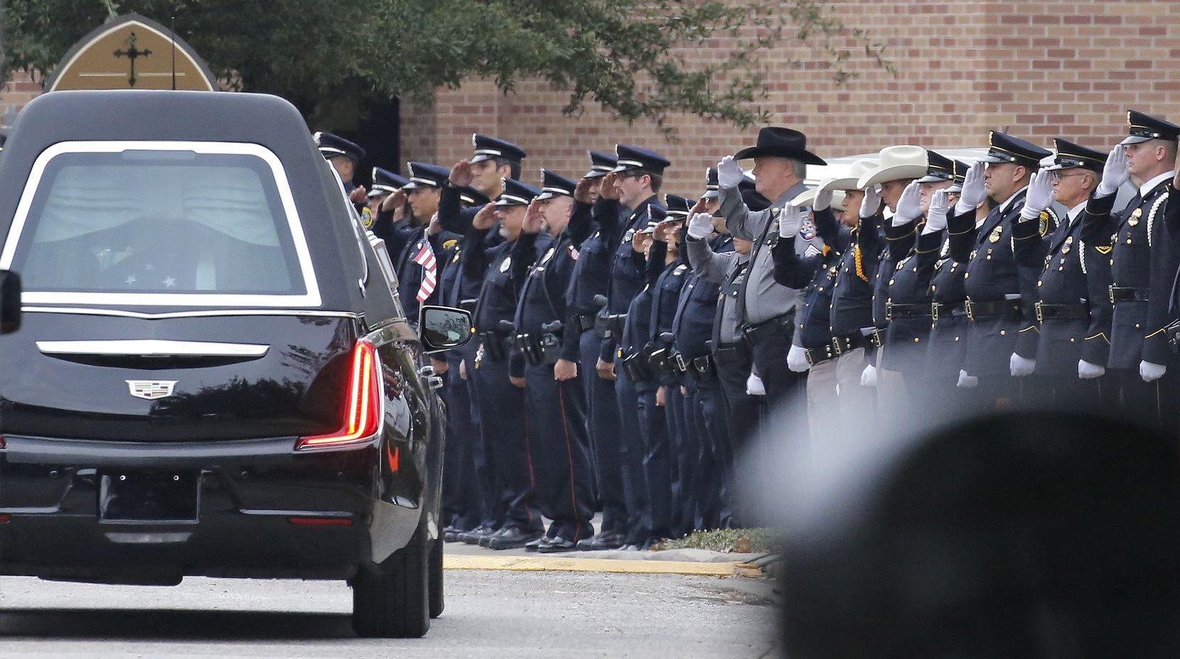 Law enforcement officers salute as the hearse drives slowly away from the church after the funeral service for George H.W. Bush, the 41st President of the United States, at St. Martin's Episcopal Church in Houston on Thursday, December 6, 2018. (Louis DeLuca/The Dallas Morning News)