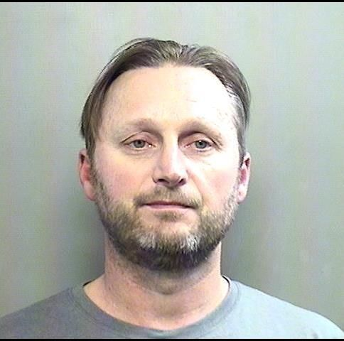 Michael Queen, 44, was arrested Jan. 30 in Arlington after police say they found him digging through the trash to steal sensitive documents.