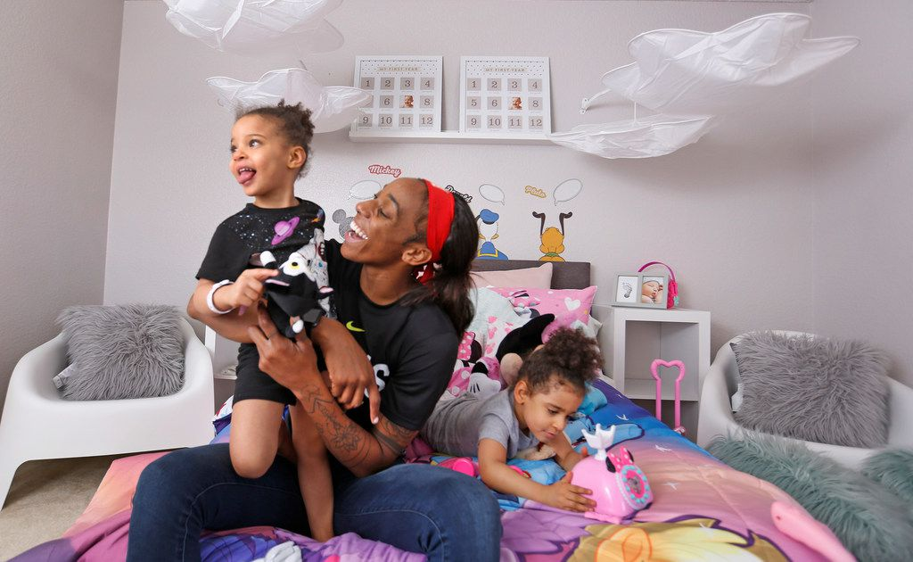 Dallas Wings' player Glory Johnson plays with her twin daughters Ava, left, and Solei in their bedroom at their home in Arlington, Texas, on Saturday, June 30, 2018. (Louis DeLuca/The Dallas Morning News)