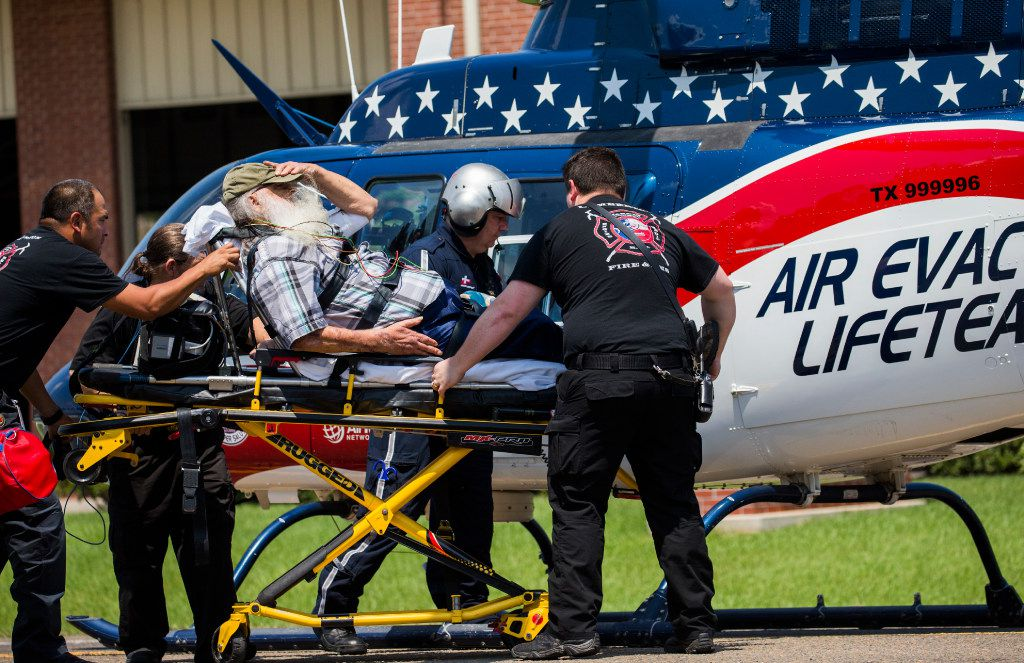 Lumberton firefighter Jordan Skinner, center, and Stephen Bradshaw, right, a rescue diver from North Carolina, and other first responders help a patient to a medical helicopter in front of the Lumberton Central Fire Department on Friday, September 1, 2017 in Lumberton, Texas. Six medical helicopters landed in front of the station on Country Lane Drive to transport critical patients to hospitals in other cities. Lumberton is isolated because of floodwaters from Hurricane Harvey. (Ashley Landis/The Dallas Morning News)