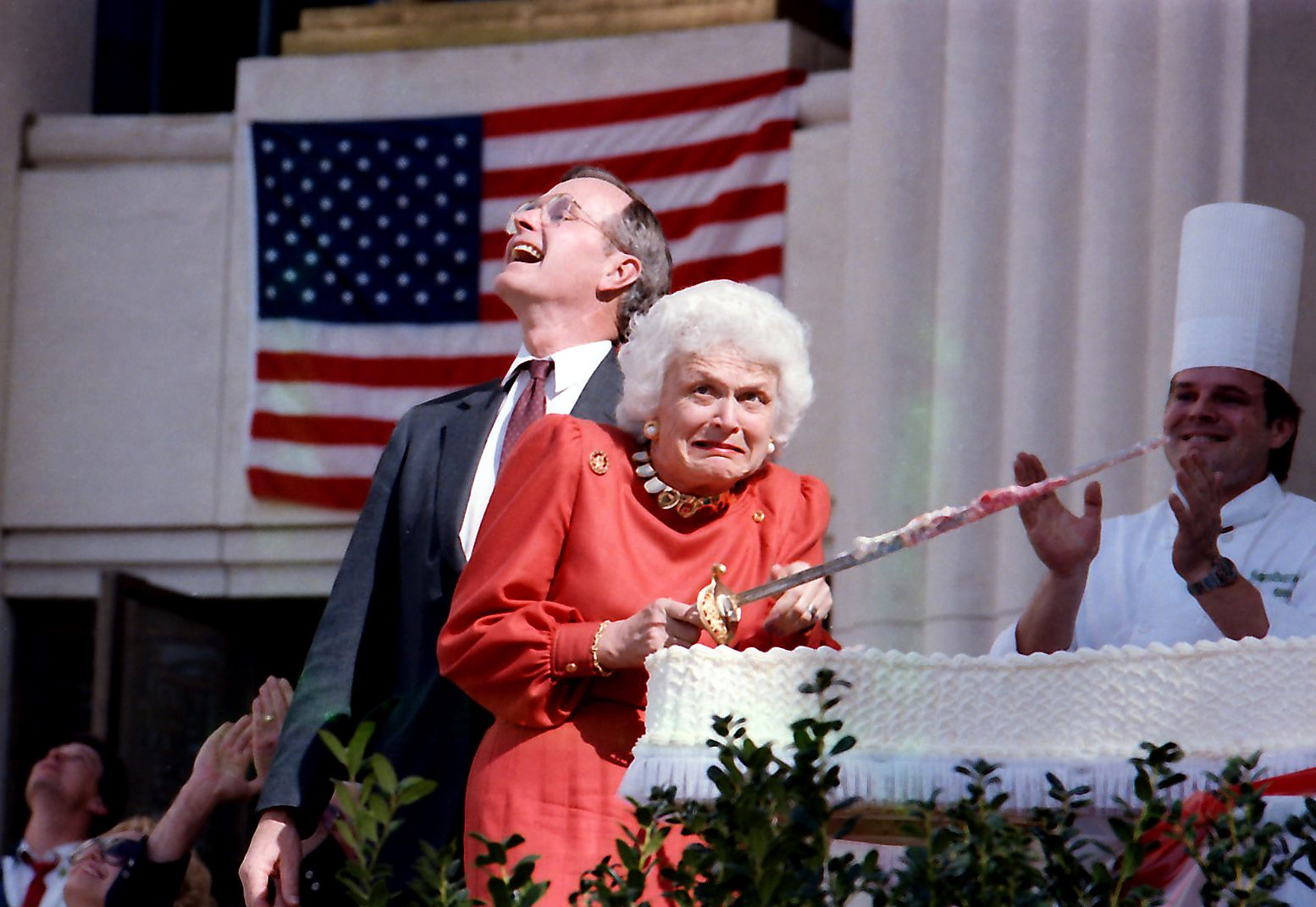 Barbara Bush cringes as a low-flying jet ceremonially passes overhead during cake-cutting ceremonies for the Texas sesquicentennial held at Fair Park on March 2, 1986. At the time, her husband, standing behind her, was vice president.