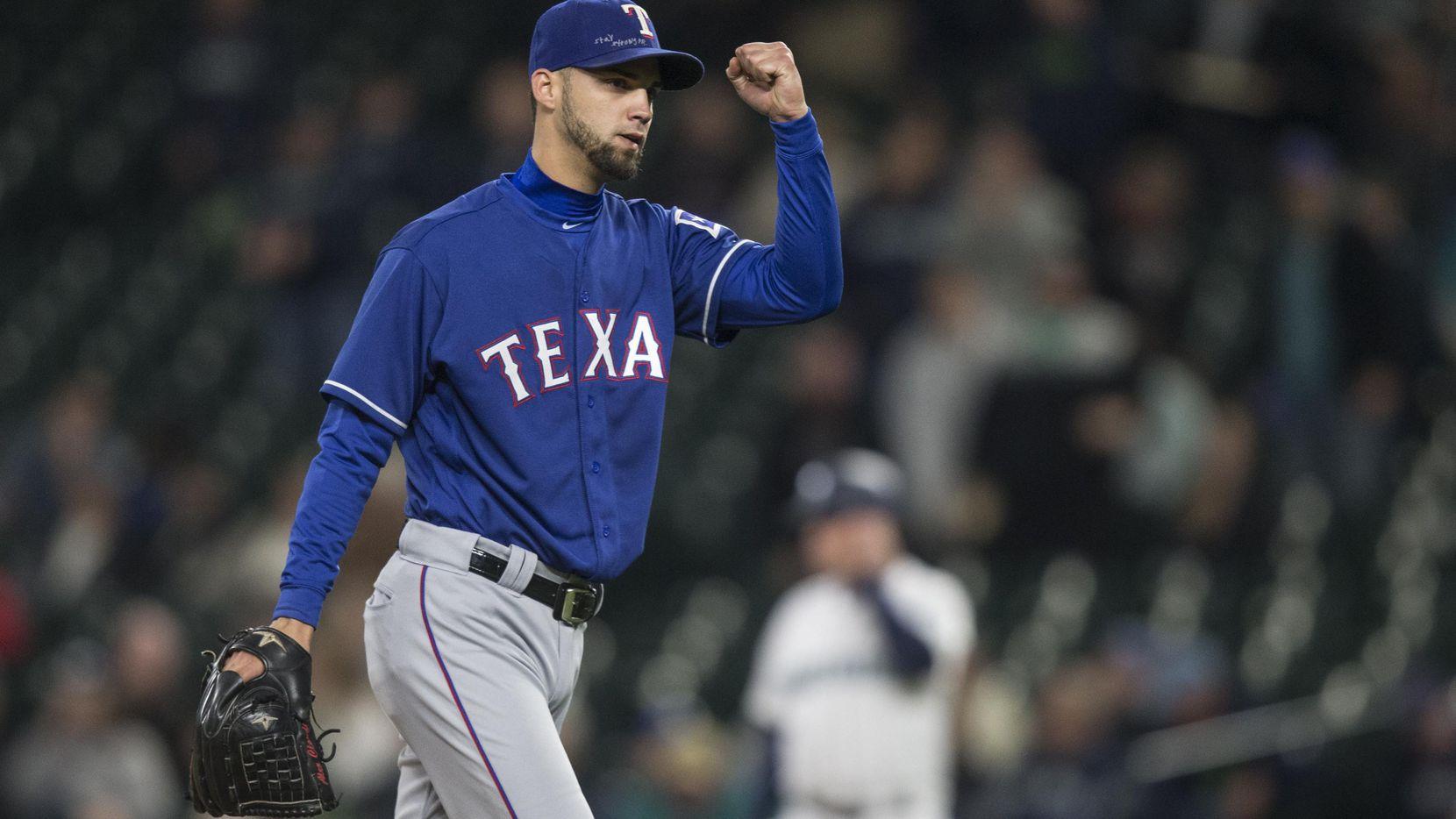 El lanzador relevista Alex Claudio levanta el brazo al asegurar la victoria de los Texas Rangers 8-6 sobre los Mariners de Seattle, el miércoles.(Getty Images)