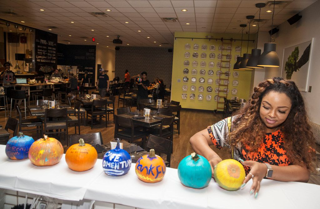 Cimajie Best, director of curriculum for Cafe Momentum, sets a recently painted pumpkin down to dry during an employee Thanksgiving dinner at Cafe Momentum.