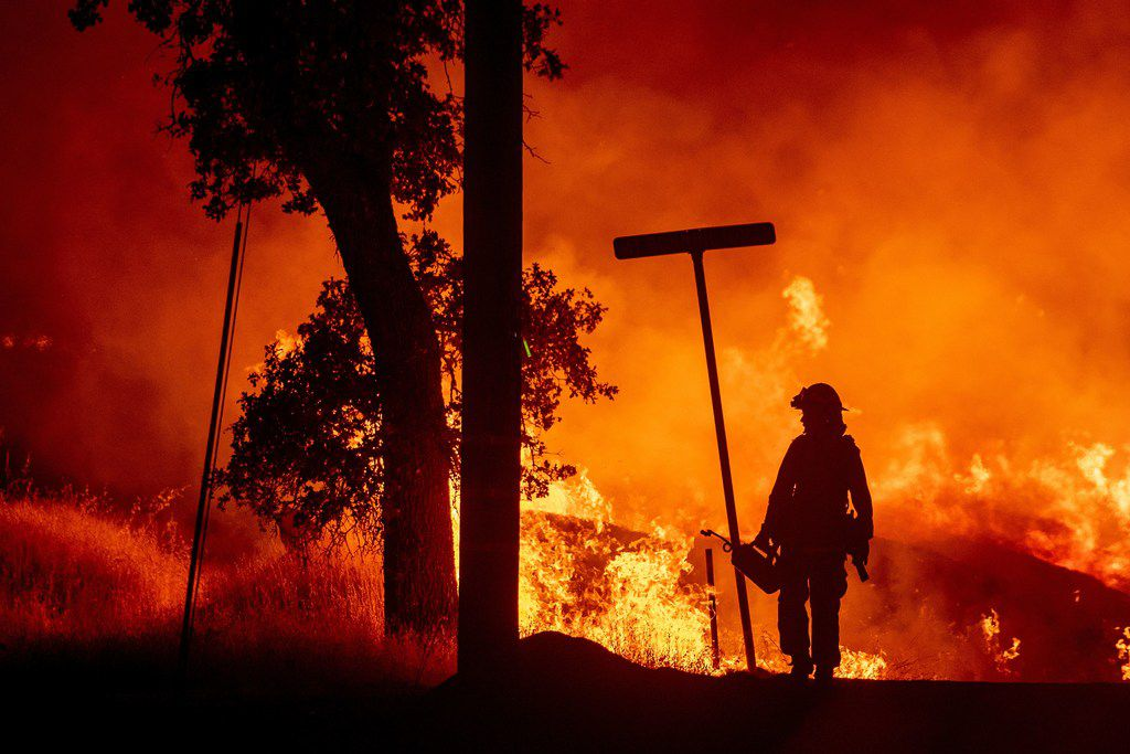 A firefighter lights backfires during the Carr fire in Redding, Calif.,on Friday. One person has died and at least two others have been injured as wind-whipped flames tore through the region.