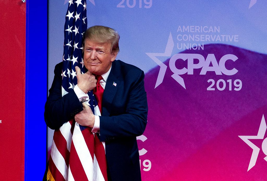 President Donald Trump hugs the American flag as he arrives on stage to speak at the Conservative Political Action Conference, CPAC 2019, in Oxon Hill, Md., on March 2, 2019.