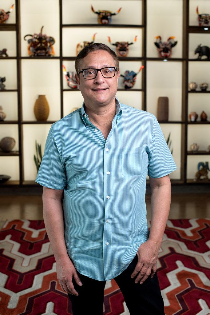 Jorge Baldor, founder of Mercado Artesanal, stands in front of hand-crafted Latin American artwork.