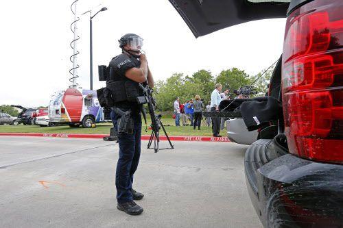 Un policía de Irving se pone un traje especial en las afueras de North Lake College poco después de reportes de un hombre armado en el campus de ese colegio comunitario.