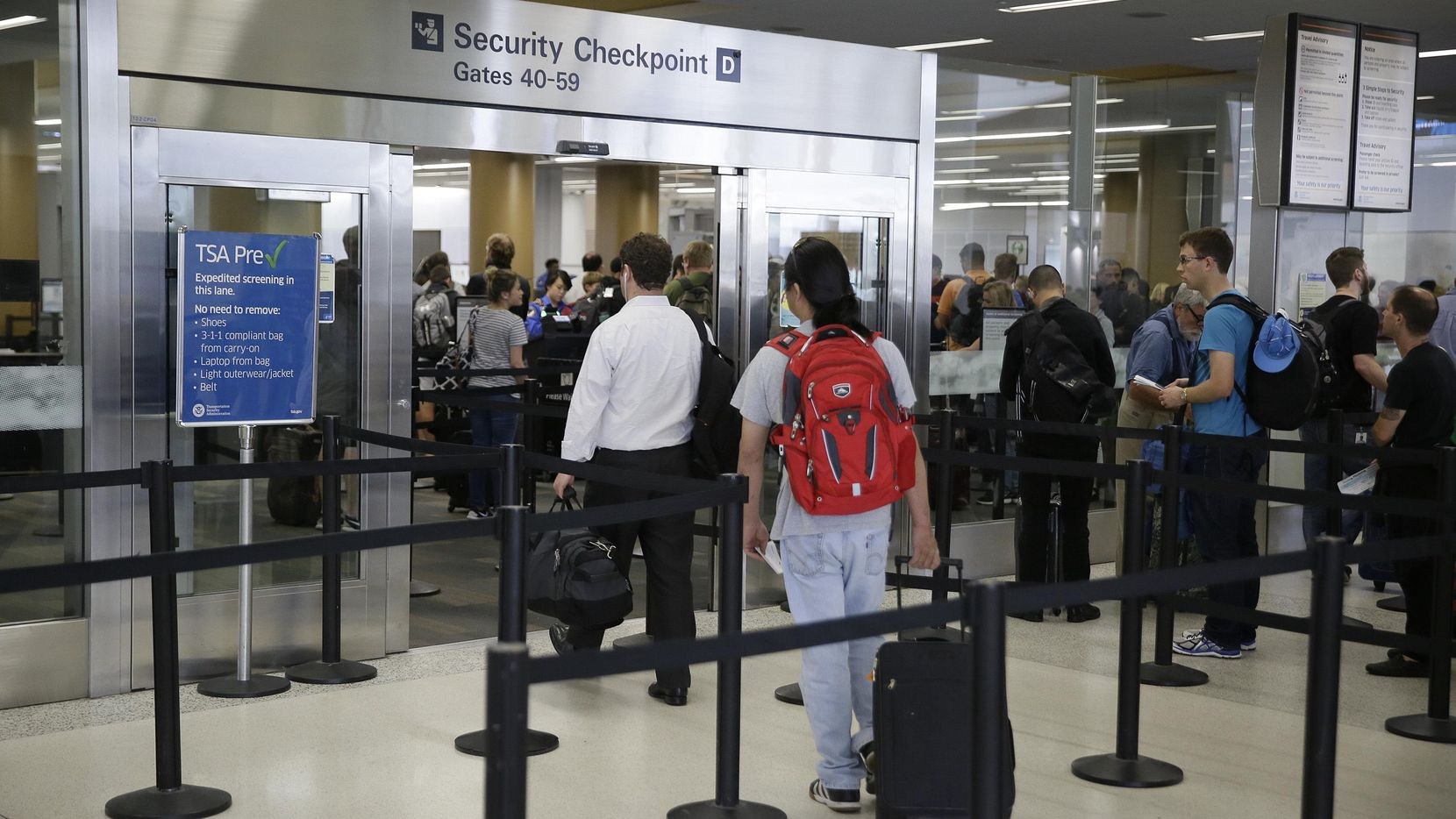 Unos viajerosn caminar por la línea de revisión de TSA, en la Terminal 2 de San Francisco. (AP/ERIC RISBERG)