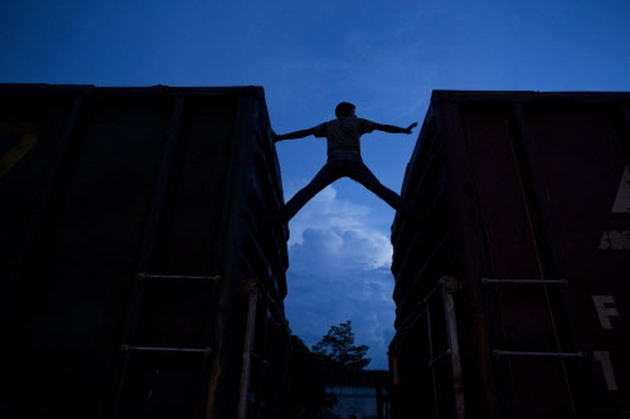 """Un inmigrante espera la llegada de un tren que lo lleve al norte en Arriaga, Chiapas, en junio del 2014, cuando la Casa Blanca describió la llegada de niños no acompañados a la frontera como una """"crisis humanitaria"""".(AP)"""