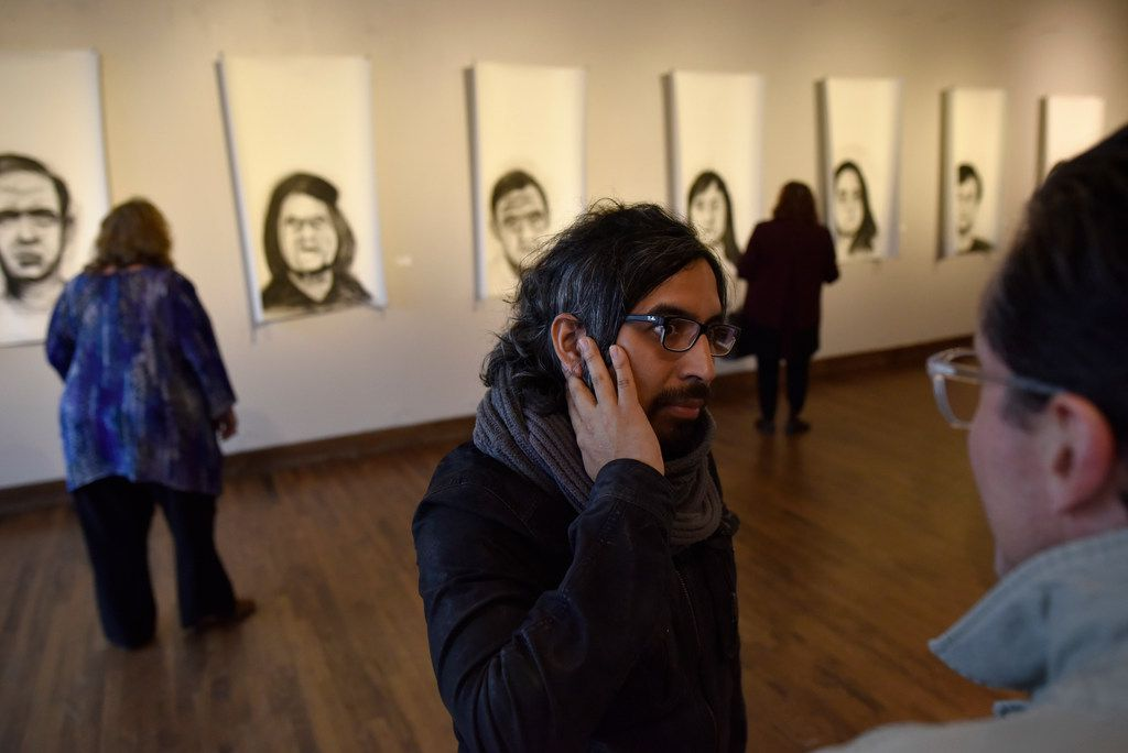Peruvian artist Rudolph Castro (center) speaks with a visitor to his art exhibition at the Oak Cliff Cultural Center. The exhibit tells the stories of families who were victims of military regimes in Latin America.