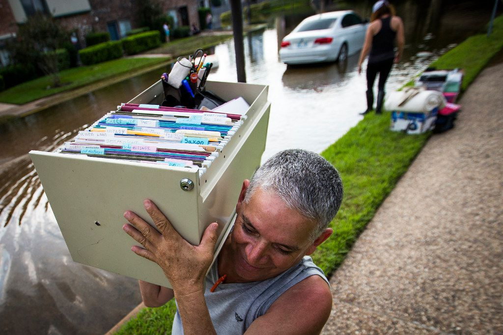 Robin Cardona retrieves belongings from his west Houston apartment through flood water from Hurricane Harvey, on Saturday, Sept. 2, 2017, in Houston.
