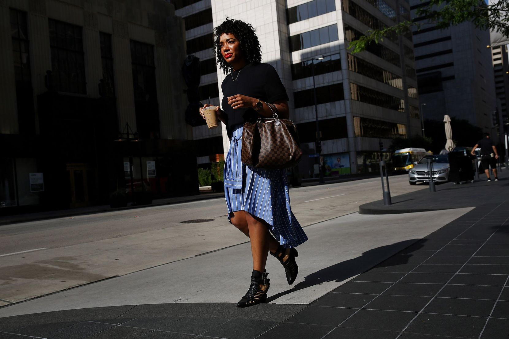 Dominique Wade,  an assistant buyer at Neiman Marcus, walks along Commerce Street on  July 7.