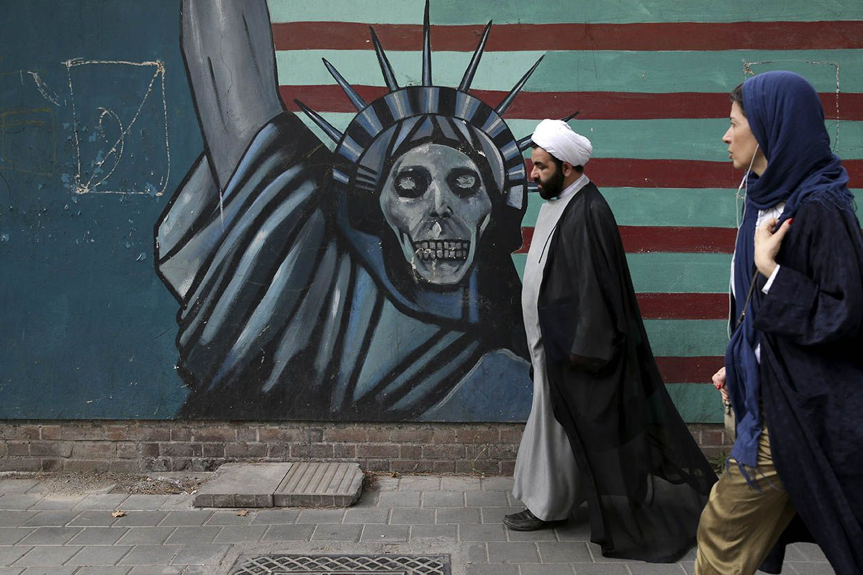 A cleric and a woman walk past an anti-U.S. mural painted on the wall of the former U.S. Embassy in Tehran, Iran, Tuesday, May. 8, 2018. President Donald Trump prepared to tell the world Tuesday whether he plans to follow through on his campaign threat to pull out of the landmark nuclear accord with Iran, as European allies braced for the potential fallout after a last-ditch persuasion effort.