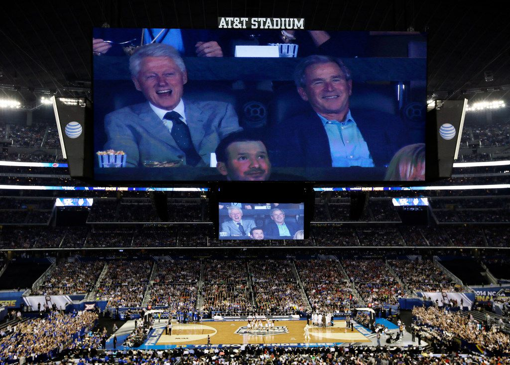 Former presidents Bill Clinton, left, and George W. Bush watch action between Connecticut and Kentucky during the first half of the NCAA Final Four tournament college basketball championship game Monday, April 7, 2014, in Arlington, Texas.