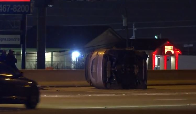 A car lies on its side after it and a Dallas police squad car crashed into each other Wednesday night in Red Bird.