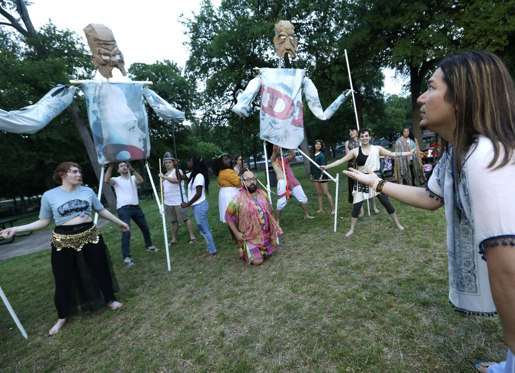 Ryan Matthieu Smith, right, directs the cast of The Bacchae in a rehearsal at Kidd Springs Park, including giant puppets representing two elders of Thebes.