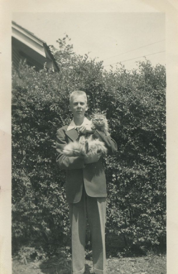 A 13-year-old Boone Pickens holds his cat, Sandy, in 1941, the year after he started his newspaper route.