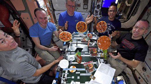 En esta foto del 18 de noviembre del 2017 proveída por la NASA, desde la izquierda, Iel estadounidense Mark Vande Hei, el ruso Serguei Ryazanskiy, el italiano Paolo Nespoli, y los estadounidenses Joe Acaba y Randy Bresnik muestran las pizzas que prepararon de cero en la Estación Espacial Internacional. Los ingredientes llegaron en noviembre en una nave comercial de suministros.  (NASA vía AP)