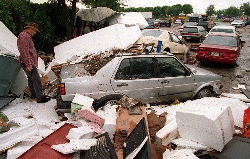 Jose Caballero, an usher at the  State Fair Music Hall, inspects his car Saturday morning. It was  caught up in floodwaters in May 1995.