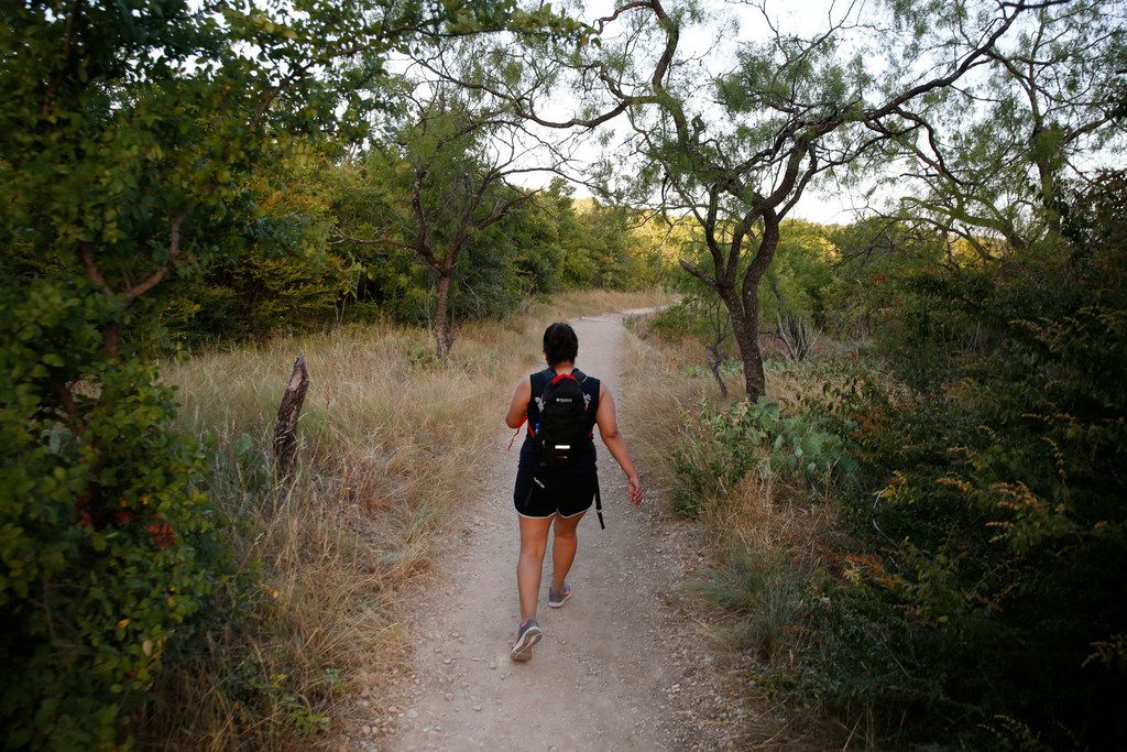 Victoria Rivera hikes along Cattail Pond Trail at Cedar Ridge Preserve in Dallas on Friday, June 29, 2018. (Rose Baca/The Dallas Morning News)