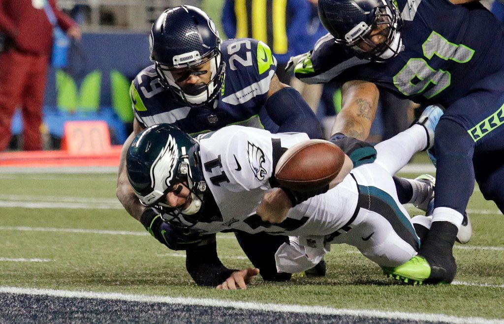 FILE - Philadelphia Eagles quarterback Carson Wentz (11) fumbles the ball near the goal line and into the end zone as Seattle Seahawks safety Earl Thomas (29) hits him during the second half of a game in Seattle on Dec. 3, 2017. (AP Photo/John Froschauer)