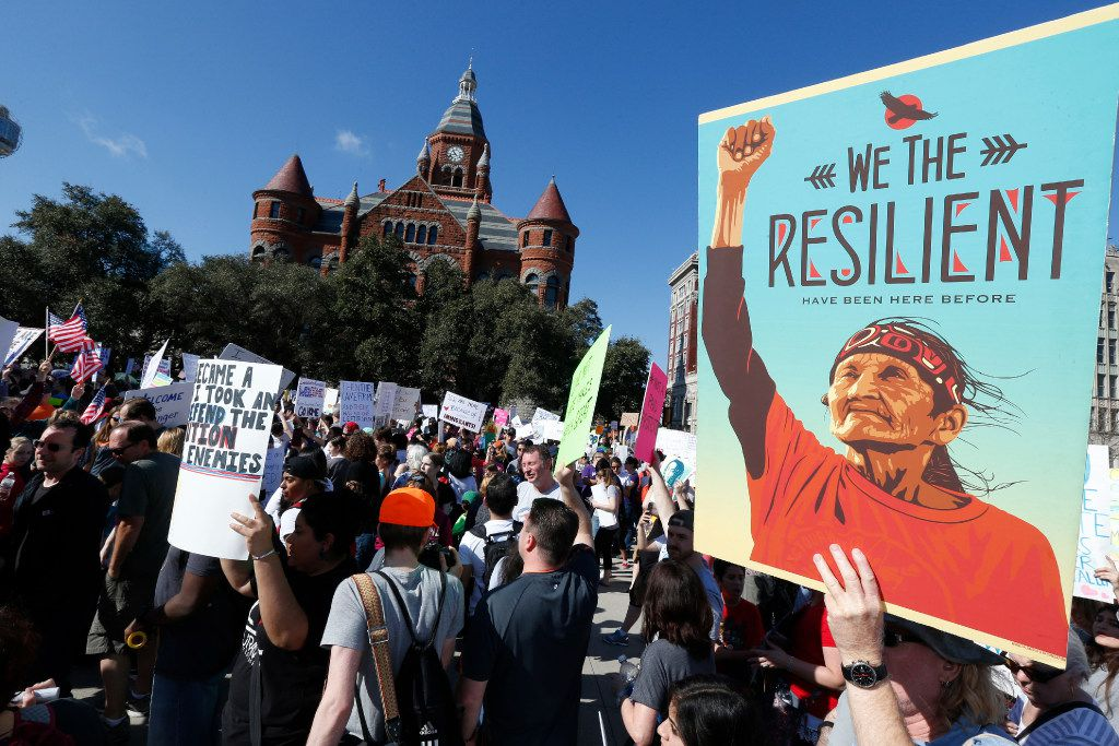 Protesters gathered to support  immigrant and refugee communities in downtown Dallas next to the JFK Memorial on Saturday.  (Nathan Hunsinger/The Dallas Morning News)