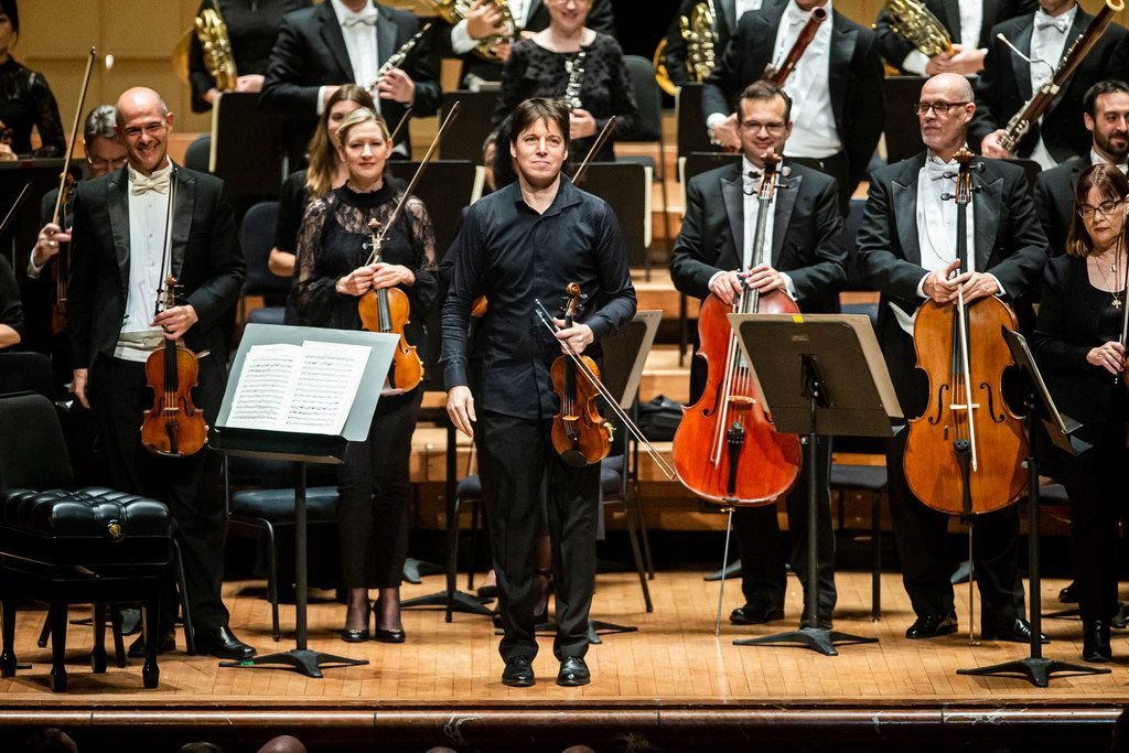 Joshua Bell (center) acknowledges the audience before serving as both the first chair violinist and conductor during a Dallas Symphony Orchestra performance at the Meyerson Symphony Center on Thursday.