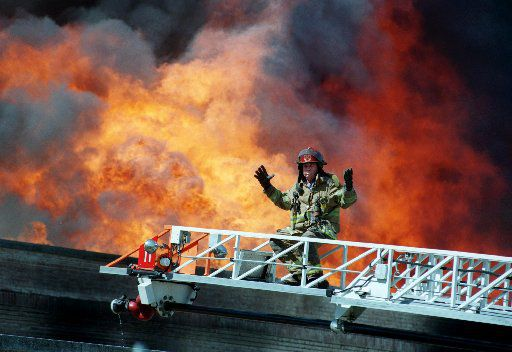 A Dallas firefighter gestures when the water pressure dropped suddenly while battling a six-alarm blaze at an the historic Crozier Tech High School in downtown Dallas Monday, April 19, 1999.