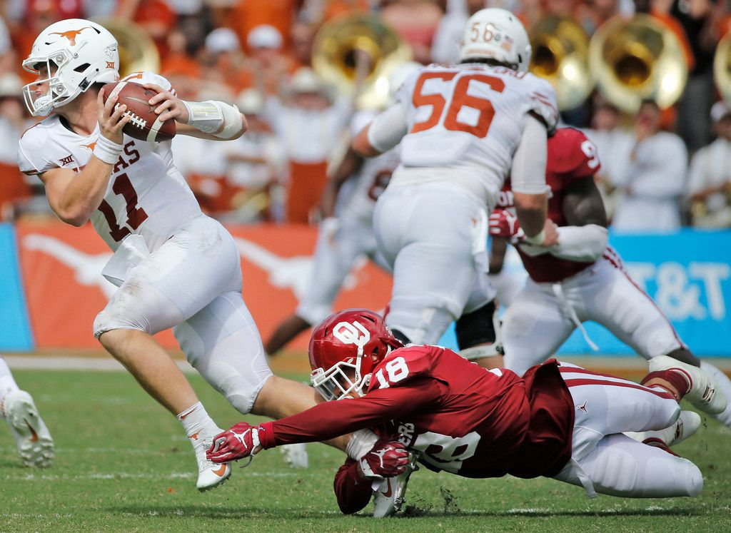 Texas Longhorns quarterback Sam Ehlinger (11) is tripped up by Oklahoma Sooners linebacker Curtis Bolton (18) on a third quarter run during the University of Texas Longhorns vs. the Oklahoma Sooners NCAA football game at the Cotton Bowl in Dallas on Saturday, October 6, 2018. (Louis DeLuca/The Dallas Morning News)