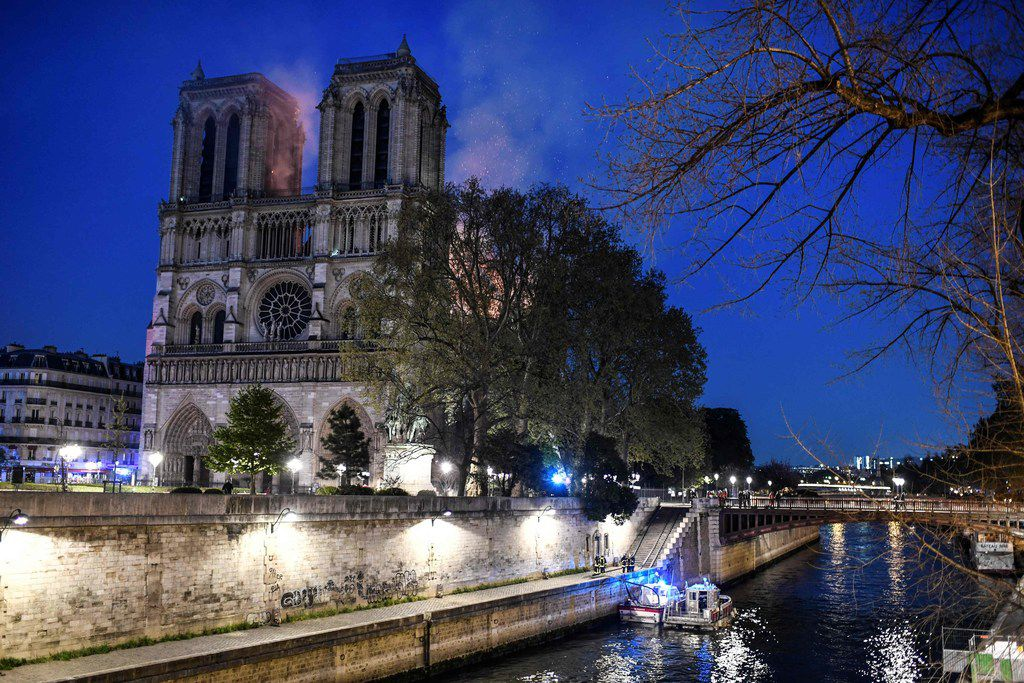 Firefighters work from a quay of the River Seine at the base of the Notre Dame de Paris Cathedral during a fire that engulfed it roof on April 15, 2019, in Paris.  A huge fire swept through the roof of the famed Notre-Dame Cathedral in central Paris on April 15, 2019, sending flames and huge clouds of grey smoke billowing into the sky.