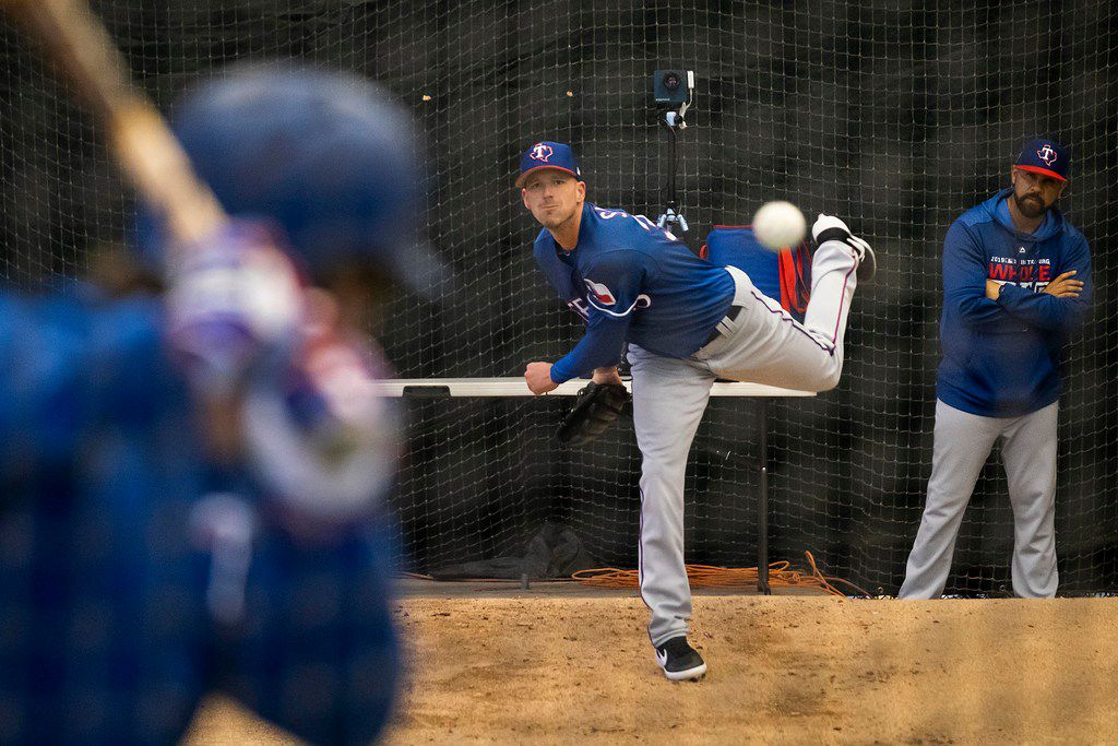 Texas Rangers pitcher Drew Smyly throws live batting practice to infielder Patrick Wisdom in the batting cages during a spring training workout at the team's training facility on Thursday, Feb. 21, 2019, in Surprise, Ariz.. (Smiley N. Pool/The Dallas Morning News)