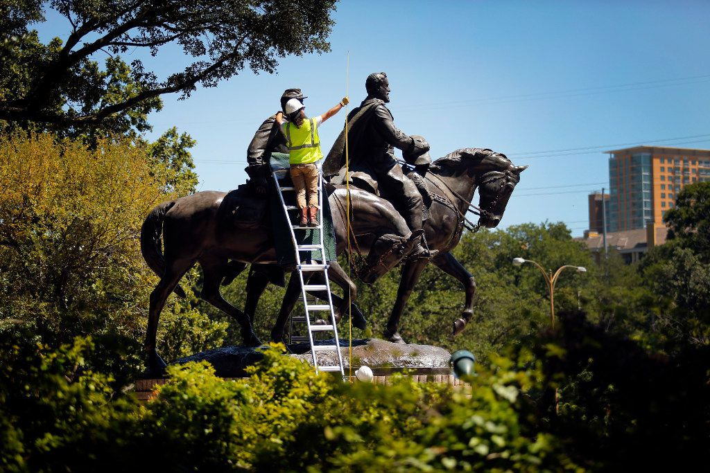 A crewman from Howell Crane and Rigging Inc measured the height of the Robert E. Lee statue at Lee Park in Dallas on Wednesday as plans were being made to remove it. (Tom Fox/Staff Photographer)