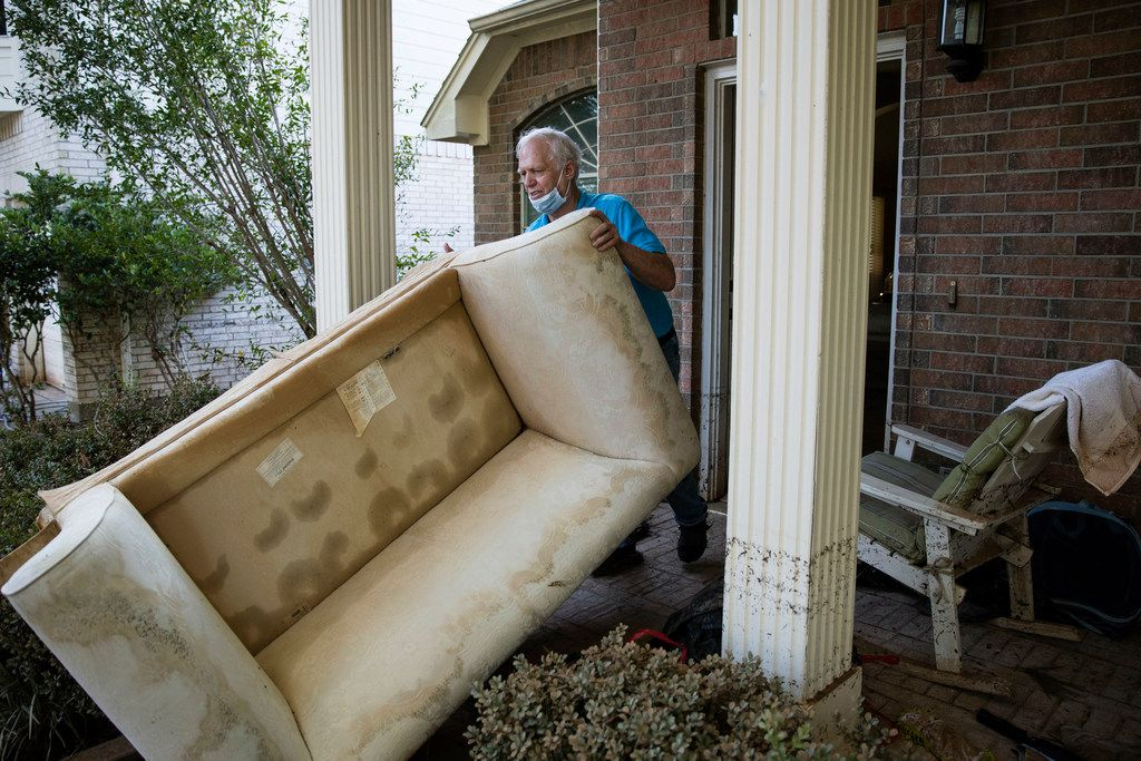Steve Thompson pushes a flood damaged couch out of his house in the aftermath of Hurricane Harvey on Thursday, Sept. 7, 2017, at the Canyon Gate community in Katy, Texas. (AP Photo/Matt Rourke)