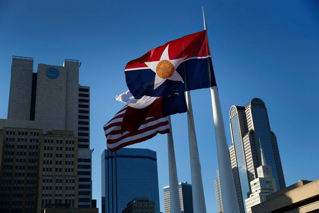 The city of Dallas flag flies alongside the Texas and U.S. flags outside Dallas City Hall.
