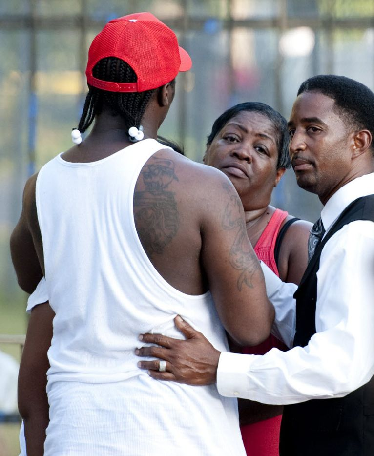 Bishop S.J. Alexander, right, prays with Lashaun Bradford and Raymon Bradford, her son, left, a cousin of James Harper, who was killed in an officer involved shooting at Dixon Avenue and Bourquin in southeast Dallas on July 24, 2012. (Jeff Lautenberger/The Dallas Morning News) 07272012xMETRO  -- police shooting of James Harper in the Dixon Circle community