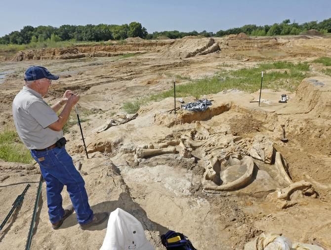 "Wayne McEwen snapped a photo Friday of the mammoth bones that were found in his gravel pit. ""It was fun just watching the volunteers,"" he said of those helping with the excavation. ""They'd come out of the pit and they were grinning from ear to ear. They were just so excited."""