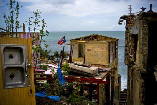 La bandera de Puerto Rico sobre escombros de una casa dañada tras el paso del huracán María en el barrio pobre de La Perla en San Juan, Puerto Rico (Foto AP/Ramon Espinosa)
